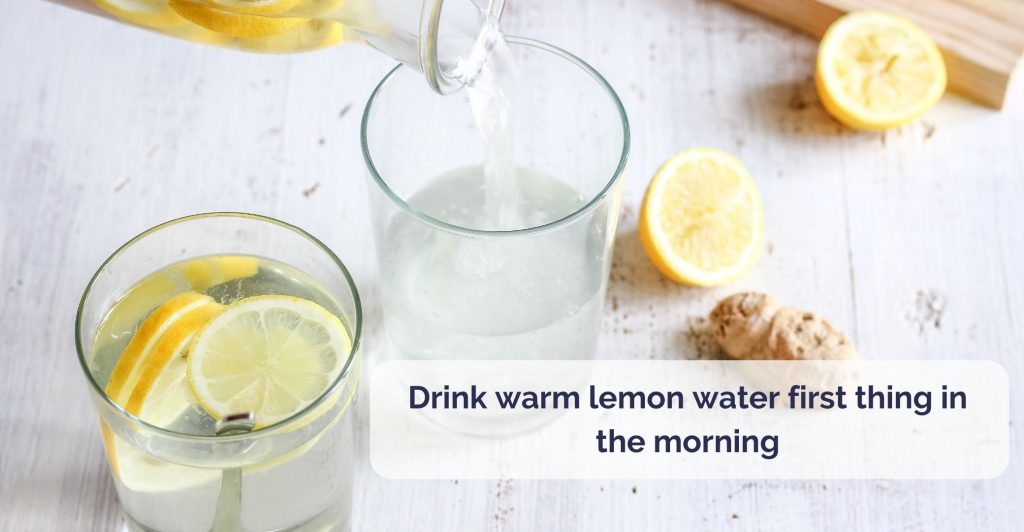 a glass of water and lemon slices, and a jug pourng more water in another glass, lemons and piece of ginger lying on the table around. Caption ' Drink warm lemon water first thing in the morning'