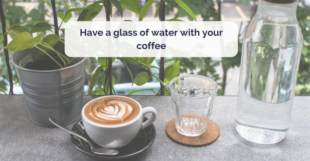 a table with a cup of artisan cappucion, glass of water and jug full of water next to it. Caption 'Have a glass of water with your coffee'