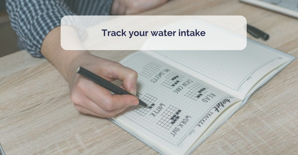 a hand writing in a paper bullet jurnal, marking water intate. Caption ' Track your water intake'