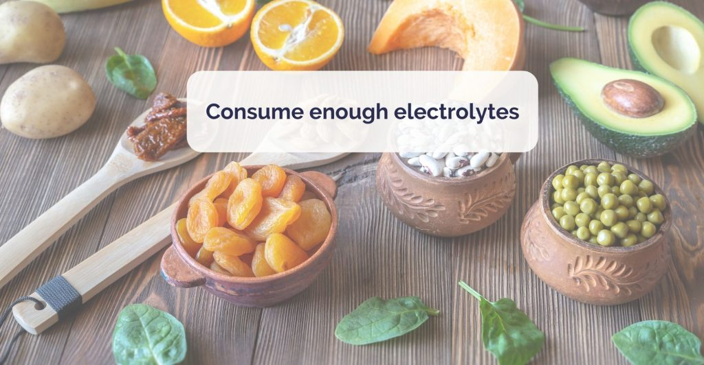 bowls of dry beans and apricots, spoonful of nuts, piece of squash, avocado, orange, potaoto and few leaves of spinach all scattered on the table. Caption ' Consume enough electrolytes'